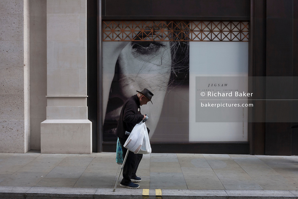 An elderly man walks bent past a large woman's face outside a soon to open Jigsaw shop in central London.