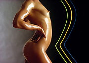 An oiled woman's nude torso against gray background with stripes of colored light in front of her