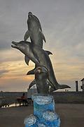 Dolphin statue ion the beach. Batumi, Georgia at sunset