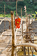 11 MARCH 2013 - LUANG PRABANG, LAOS:  A Buddhist novice walks across the bamboo foot bridge over the Nam Khan River in Luang Prabang. The bridge is a seasonal bridge. It's built when the river level recedes in the dry season and washes away every year when the river rises. It connects Luang Prabang to several small villages north of the city.   PHOTO BY JACK KURTZ