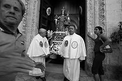 Due fedeli che accompagnano fuori dalla chiesa dell'Arcangelo Michele la statua della Madonna del Carmine. La foto è stata scattata a Mesagne (Br) il 15-07-2010 durante la celebrazione della festa in onore della Santa protettrice del paese.