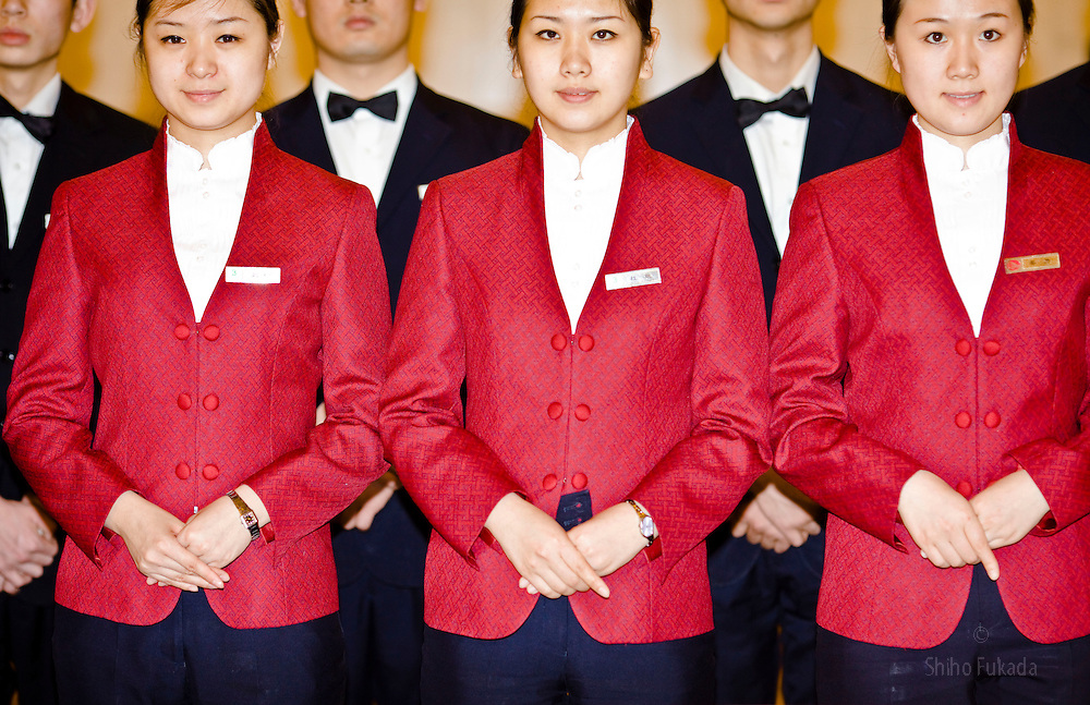 Attendants stand in line after their duty to serve tea to delegates at the Great Hall of the People during the Chinese People's Political Consultative Conference (CPPCC), plenary session for NPC, in Beijing, China.