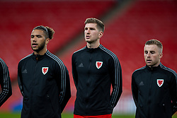 LONDON, ENGLAND - Thursday, October 8, 2020: Wales' Tyler Roberts, Chris Mepham and Joseff Morrell line-up for the national anthem before the International Friendly match between England and Wales at Wembley Stadium. The game was played behind closed doors due to the UK Government's social distancing laws prohibiting supporters from attending events inside stadiums as a result of the Coronavirus Pandemic. England won 3-0. (Pic by David Rawcliffe/Propaganda)