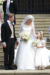 Newlyweds Thomas Kingston and Lady Gabriella Windsor with a young bridesmaid on the steps of the chapel after their wedding at St George's Chapel in Windsor Castle.