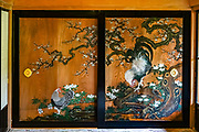 Art work on large sliding screens. Tamozawa Imperial Villa (Tamozawa Goyotei) blends traditional Edo and early modern Meiji Period architecture throughout its 106 rooms. The villa was erected in Nikko in 1899, using parts of a residence that originally stood in Tokyo, Japan. Before being moved to Nikko, the building served initially as the Tokyo residence of a branch of the Tokugawa family and was later temporarily used as the Imperial Palace. In Nikko, it was enlarged into a summer residence and retreat for the Imperial Family, but suffered neglect after World War II. In 2000, the villa was opened to the public after extensive renovation works. Tamozawa Imperial Villa is one of the largest remaining wooden buildings in Japan. The interior of the villa is a curious mix of Japanese and Western styles: many floors are carpeted and elaborate chandeliers hang from the ceilings, yet Japanese elements include sliding paper doors and tatami flooring. Although still impressive in size and grandeur, Tamozawa Imperial Villa currently occupies only one third of its original area. It now functions as a museum and memorial park.