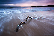 There was nothing set up about this image. The wood was actually there, partially embedded in the soft sands of Silver Bay as the waves washed over it on the incoming tide. In the background a gentle sun illuminated the rear of a heavy blanket of rain cloud, sending a pink glow into the air. The shift between the warm and cool ends of the spectrum were subtle and delicate, absolutely beautiful.