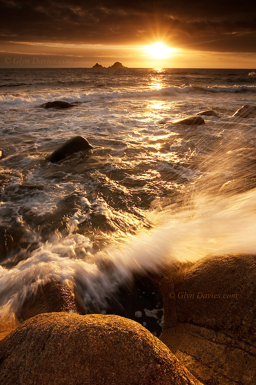 Sunset over the Brison rocks seen from Porth Nanven, SW Cornwall.