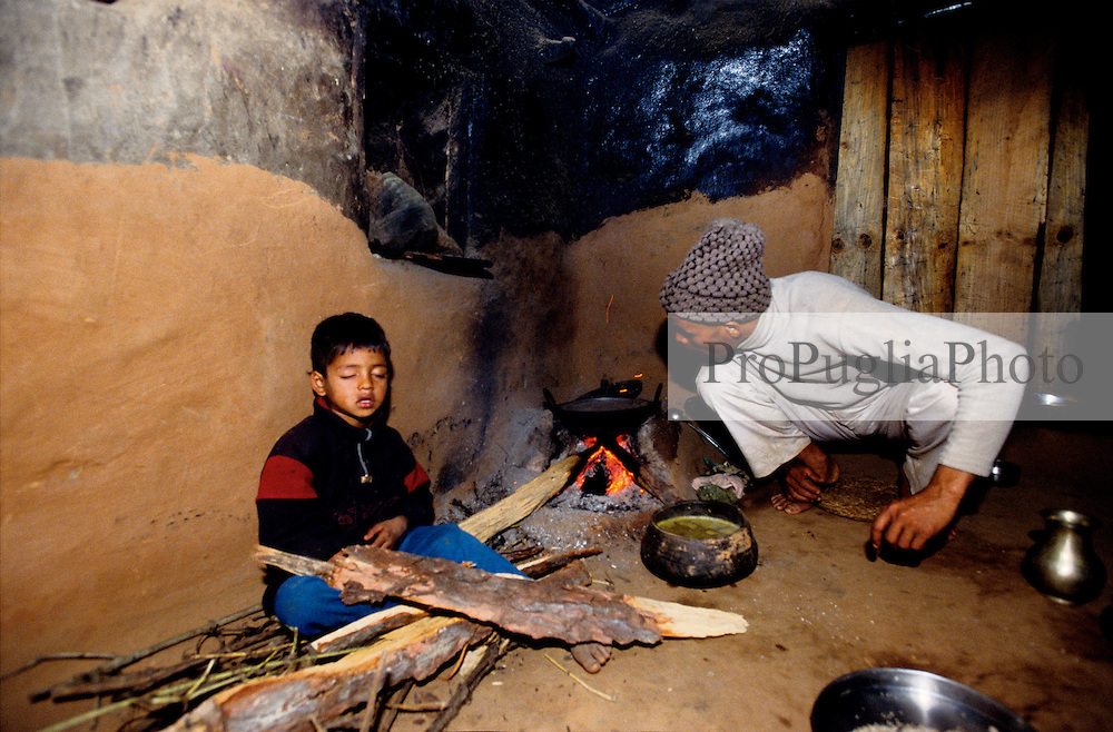 Dailekh 02 March 2005... A Nepali lights a fire in the kitchen, he is preparing the typical national food 'Khana' rice, lentils and potatoes. His son is falling asleep.