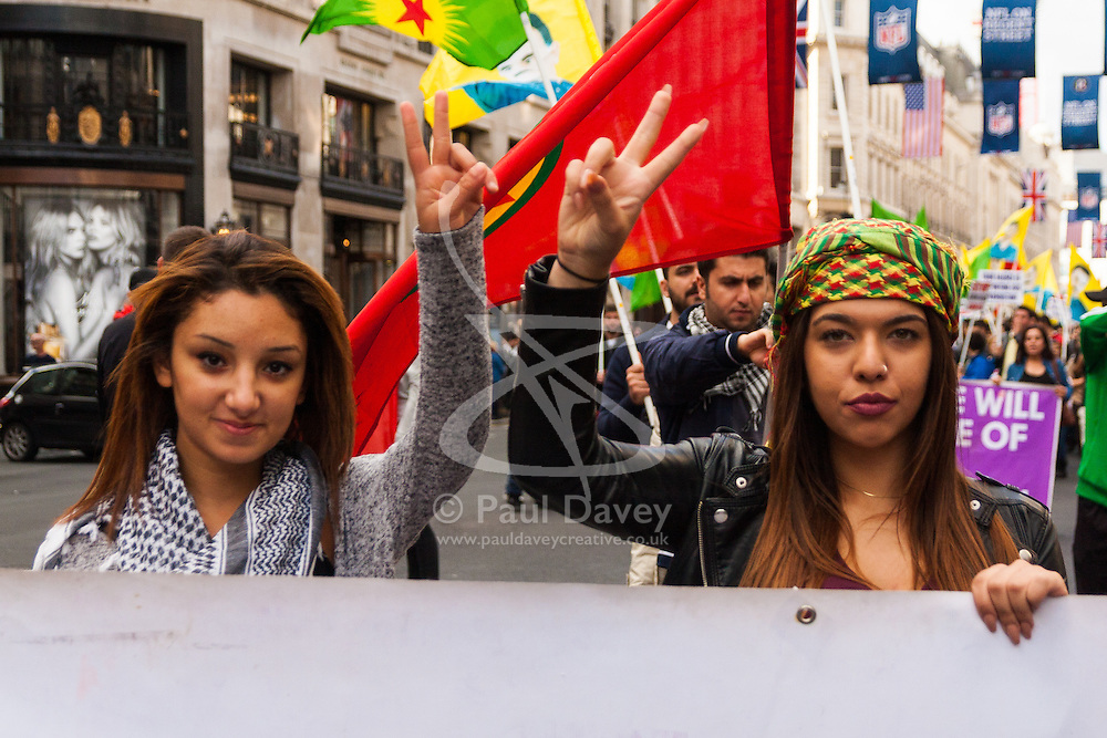 "London, October 19th 2014. Hundreds of London's Kurdish community march throgh the capital in protest against ISIS and the Turkish government who they accuse, by not getting involved in military action against ISIS, of using the Jihadists to wipe out Kurds who have long been campaigning for an independent Kurdistan. PICTURED: Two young women give the ""v"" for victory sign as they march along Regents Street."