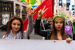 """London, October 19th 2014. Hundreds of London's Kurdish community march throgh the capital in protest against ISIS and the Turkish government who they accuse, by not getting involved in military action against ISIS, of using the Jihadists to wipe out Kurds who have long been campaigning for an independent Kurdistan. PICTURED: Two young women give the """"v"""" for victory sign as they march along Regents Street."""