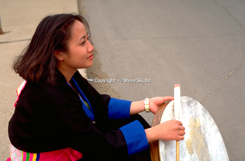 Resting drummer age 19 at the Asian American Festival.  St Paul  Minnesota USA