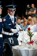 A ROTC cadet lights a candle at The Missing Man table during the Memorial Day Service at the National World War II Museum in New Orleans, LA.