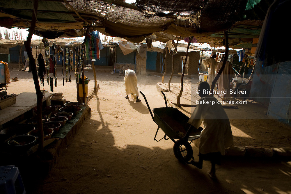 Busy residents and workers of the shaded souk market of the 4 sq km Abu Shouk refugee camp which is (disputedly) home to 38,000 displaced persons and families on the outskirts of the front-line town of Al Fasher (also spelled, Al-Fashir) in north Darfur. .