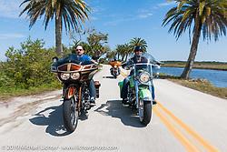 Brian and Laura Klock ride their custom bikes side by side through Tomoka State Park during Daytona Bike Week. FL, USA. March 11, 2014.  Photography ©2014 Michael Lichter.