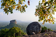 A Sri Lankan guide leads a family with two children down from the top of Pidurangala Rock. The peak is popular for its excellent view of the Sigiriya rock fortress (left side of image), one of Sri Lanka's iconic landmarks.