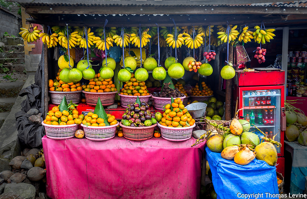 Bali fruit stand with hanging fruit and also in baskets.