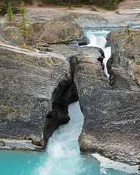 The Kicking Horse River flows under a Natural Bridge as a tumbling waterfall in Yoho National Park