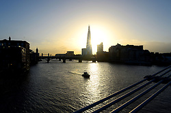 The sun rising behind The Shard from Millennium Bridge over the river Thames in the morning. London, United Kingdom. Thursday, 14th November 2013. Picture by Ben Stevens / i-Images