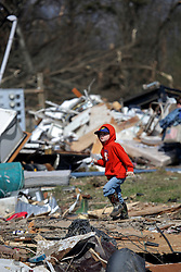 24 February 2016. Sugar Hill RV Park, Convent, Louisiana.<br /> Scenes of devastation following a deadly EF3 tornado touchdown. 2 confirmed dead. <br /> Youngster Garrett Brown (4 yrs) looks for his toys and helps his family recover all they can from their destroyed trailer.<br /> Photo©; Charlie Varley/varleypix.com