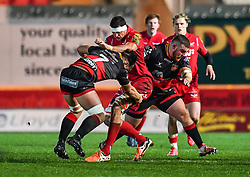 Scarlets' Aaron Shingler is tackled by Dragons' Lloyd Fairbrother and Taine Basham<br /> <br /> Photographer Craig Thomas/Replay Images<br /> <br /> Guinness PRO14 Round 13 - Scarlets v Dragons - Friday 5th January 2018 - Parc Y Scarlets - Llanelli<br /> <br /> World Copyright © Replay Images . All rights reserved. info@replayimages.co.uk - http://replayimages.co.uk