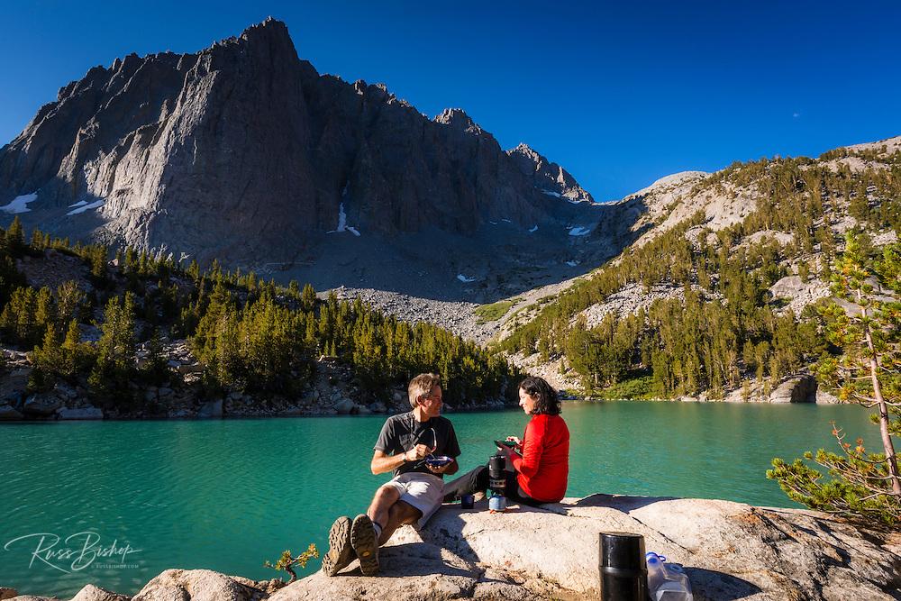 Hikers enjoying breakfast at Big Pine Lake #3, John Muir Wilderness, Sierra Nevada Mountains, California USA
