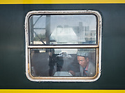 A Uighur man blows the sand off the edge of his window. Life inside the train - mostly Muslim Uighur people  ride this train.