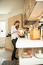 Young woman preparing food in kitchen, Munich, Bavaria, Germany