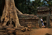 Tourist in ruined doorway in Ta Prohm, Angkor temple complex<br /> Unlike most of the temples of Angkor, Ta Prohm has been largely left to the clutches of the living jungle. With its dynamic interaction between nature and man-made art, this atmospheric temple is a favorite for many - who can't help but feel a little like Indiana Jones or Lara Croft (which was filmed here) as they pick through the rubble.<br /> Construction on Ta Prohm began in 1186 AD. Originally known as Rajavihara (Monastery of the King), Ta Prohm was a Buddhist temple dedicated to the mother of King Jayavarman VII.