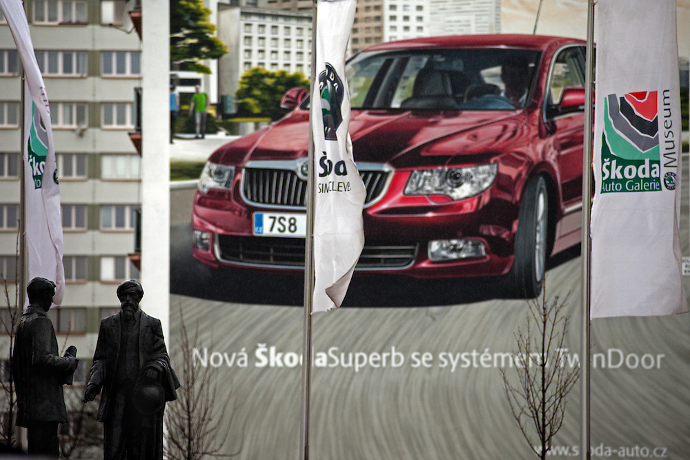 Die Skulpturen von den Skoda Gruendern Vaclav Klement und Vaclav Laurin vor dem Skoda Automuseum in Mlada Boleslav. Im Hintergrund Werbung fuer den neuen Skoda Superb. Mlada Boleslav liegt noerdlich von Prag und ist ungefaehr 60 Kilometer von der tschechischen Haupstadt entfernt. Skoda Auto beschäftigt in Tschechien 23.976 Mitarbeiter (Stand 2006), den Grossteil davon in der Zentrale in Mlada Boleslav. Damit sind mehr als 3/4 aller Erwerbstätigen der Stadt in dem Automobilkonzern tätig.<br /> <br />                                      Skoda founders Vaclav Laurin and Vaclav Klement infront of a bigboard commercial for the Skoda Superb at a panel house close to the Skoda factory in the city of Mlada Boleslav. The city is located north of Prague and about 60 km away from the Czech capital. Skoda Auto has about 23.976 employees (2006) in Czech Republic and a big part of them is working in Mlada Boleslav. 3/4 of the working population in Mlada Boleslav is working for the Skoda Auto company.