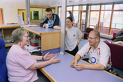 Group of youths chatting to receptionist at day centre for homeless and vulnerably housed young people,