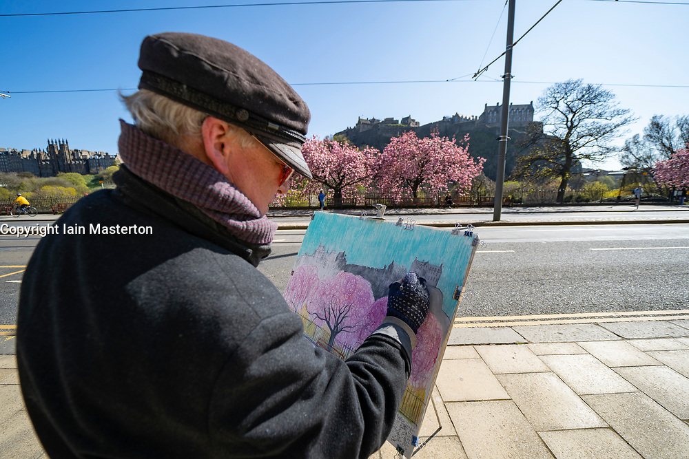 Edinburgh, Scotland, UK. 25 April 2021. Scenes from streets of Edinburgh city centre on Sunday afternoon on the day before non-essential shops and businesses can reopen in Scotland under relaxed covid-19 lockdown rules. Pic An artist painting cherry blossom on Princes Street. Iain Masterton/Alamy Live News