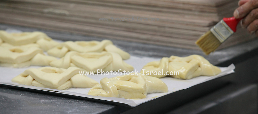 The shaped pastries are allowed to leaven before baking, glazing has been applied Photographed at a boutique bakery