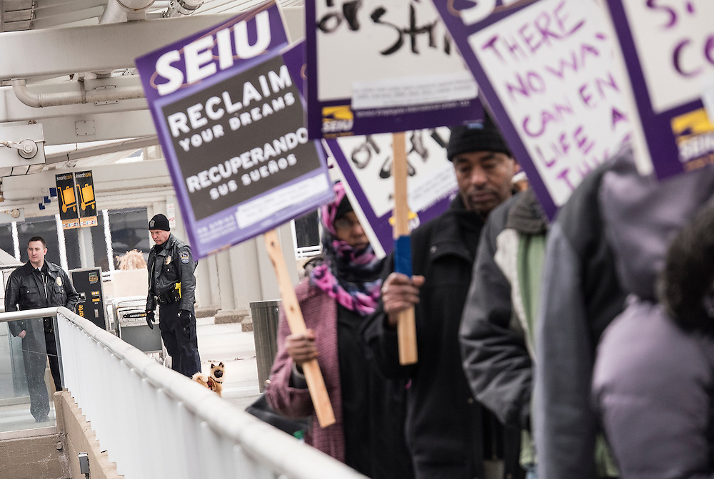 Airport police officers keep an eye on Twin Cities janitors represented by Service Employees International Union, as well as some supporters, as they picket for a wage increase at Minneapolis-St. Paul International Airport's Terminal 1 February 17, 2016.