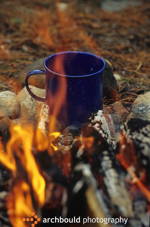 Cup warms beside an open campfire