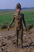 AREJM5 Child playing in mud pool
