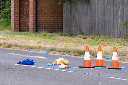 © Licensed to London News Pictures. 27/07/2021. Stoke Poges, UK. Medical waste and an evidence bag inside a cordon at the scene on Bells Hill in Stoke Poges, Buckinghamshire, following an assault on Monday 26 July at approximately 21:30BST. A man in his twenties suffered a serious leg injury following the assault which is understood to have involved a machete. Two men, aged 19 and 21, and a 20-year-old woman have been arrested on suspicion of section 18 wounding with intent. Photo credit: Peter Manning/LNP