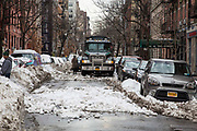A large black Mack hauling truck driving through the snow on 34 West 13st Street New York City,  New York, United States of America, after the snowstorm in January 2016.  There are cars parked on both sides of the street buried in snow. The snowstorm brought more than 2 feet of snow in many areas, which broke many records.