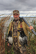 Successful waterfowl hunter with the results of a morning shoot on the Delta Marsh in Manitoba.