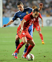 Fernando Ruben Gago, back, challenges Andy Nagelein of Hong Kong during a friendly football match in Hong Kong, China, 14 October 2014.<br /> <br /> Lionel Messi needed just six minutes to make his mark in Argentina's 7-0 rout of Hong Kong in a friendly at Hong Kong Stadium on Tuesday (14 October 2014). The Barcelona star Messi scored twice after going on as a substitute for the last 30 minutes of the game to celebrate the 100th anniversary of the Hong Kong Football Association. Napoli striker Gonzalo Higuain and Benfica's Nicolas Gaitan also scored two goals each after Sevilla's Ever Banega had opened scoring in the 19th minute.