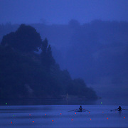 Rowers training on the water at dawn on Lake Karapiro, near Cambridge, Waikato. Many national and international rowing competitions are held on Lake Karapiro which is also the home of The Rowing New Zealand High Performance Centre. Lake Karapiro hosted the 2010 World Rowing Championships. Lake Karapiro, Waikato,  New Zealand. 13th December 2010. Photo Tim Clayton