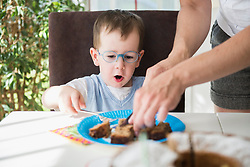 Mother and son having a slice of cake of birthday cake, Bavaria, Germany