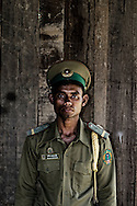Portrait of a guard in uniform standing in front of a wooden wall, Sekong Province, Laos, Southeast Asia