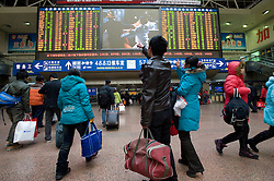 Passengers checking train departure times inside Beijing Railway station during peak travel season at Chinese New Year in 2009