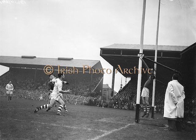 Two players tackle near the goal as goalie jumps high during the All Ireland Senior Gaelic Football Championship Final, Cork v Galway in Croke Park on the 7th October 1956. Galway 2-13 Cork 3-7.