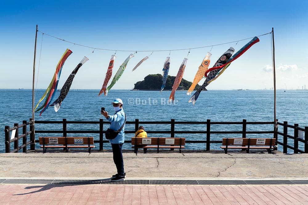 person making a selfie with Koinobori fluttering in the wind Tokyo bay water front  Yokozuka Japan