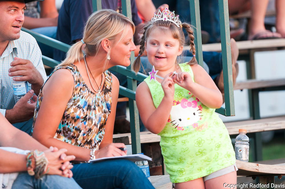 Jessica watches her husband and son compete from the bleachers. A friendly girl shares a secret with her.