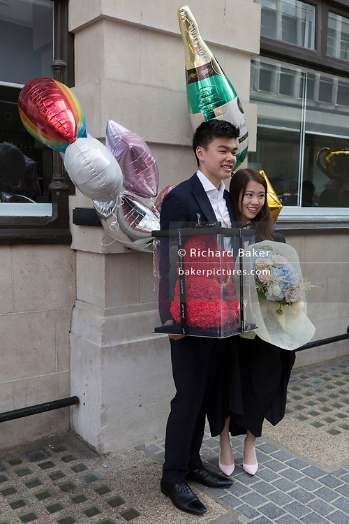 Hillary Chung (right), a 21 year-old Law graduate from Hong Kong, celebrates her graduation with a 2:1 degree outside the London School of Economics (LSE) after her graduation ceremony, on 22nd July 2019, in London, England.