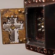 """The Eva Braun crucifix hangs in the middle of the aperture gate. Evas glass and gold """"EB"""" monogram is in the middle of the crucifix. <br /> The script on the brass gate holding the crucifix  reads; <br /> """"There are no angels. There are no Devils.<br /> Just scattered tailings of words, myth, tears and soil.<br /> With all of creation made to be broken,<br /> blessed are those who sing in Gods killing jar."""""""