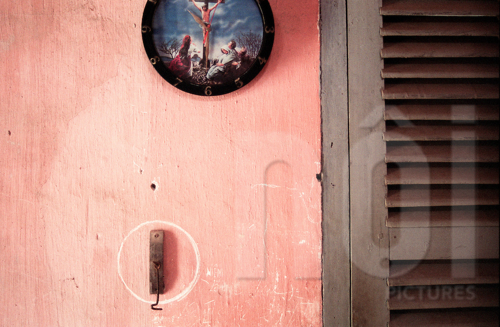 Clock sticked on a pink wall with a crucifixion scene in its frame. Nam Dinh province, Vietnam, Asia