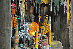 Small statue of Buddha at Banteay Kdei temple, Angkor Wat, currently used for worship, covered with bright orange cloth and many colorful hangings, in ancient setting